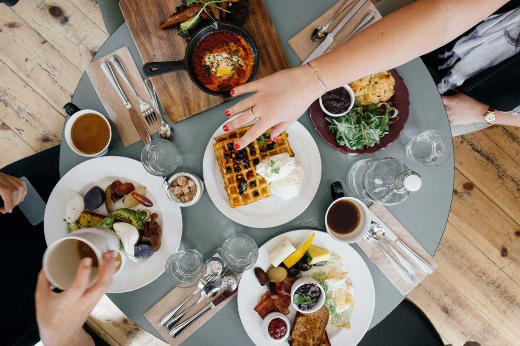 table remplie d'assiettes de nourriture et des mains qui se servent