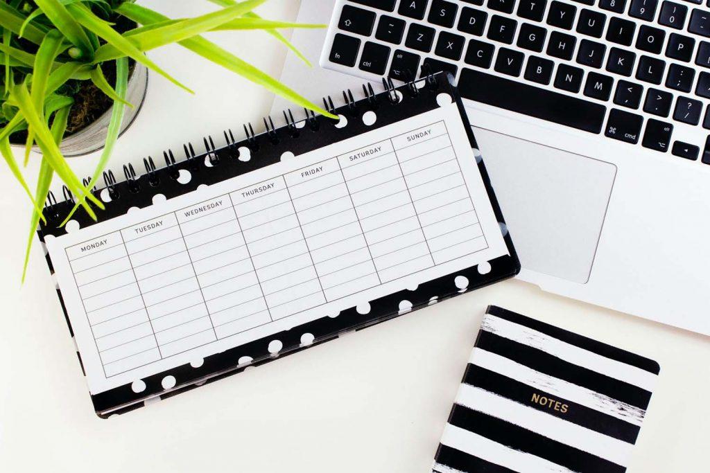 planning de semaine avec un ordinateur et un bloc notes pour planifier ses repas