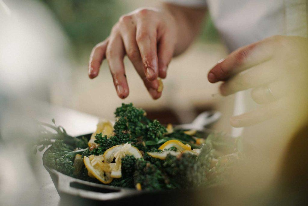 mains qui preparent une salade de kale