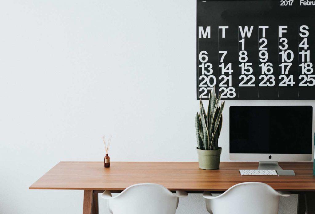 bureau propre et rangé avec ordinateur et calendrier