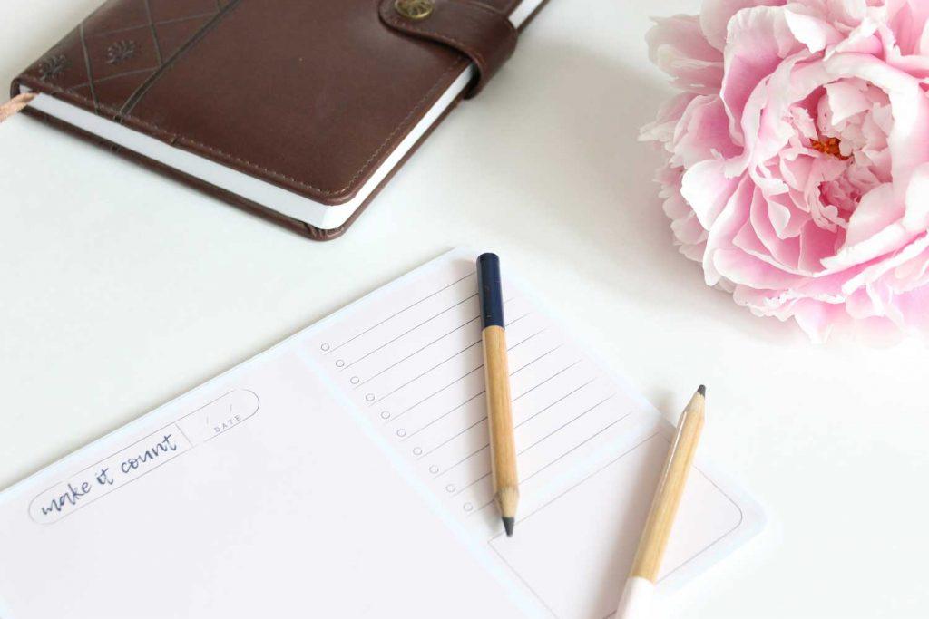 crayons et agenda sur une table avec une fleur rose