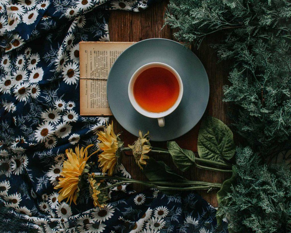 tasse de the sur un livre et des fleurs